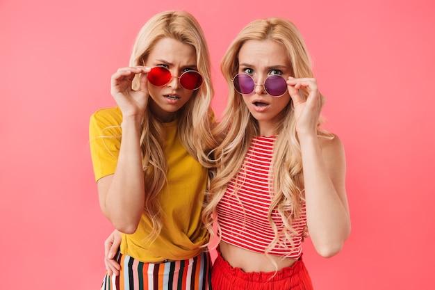 Obraz zszokowanych blond bliźniaków w okularach przeciwsłonecznych na różowej ścianie