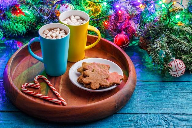 Obrazek drewnianego stołu ze świątecznymi ciasteczkami, dwa kubki z kakao z pianką, pałeczki karmelu, gałązki świerku z płonącą girlandą