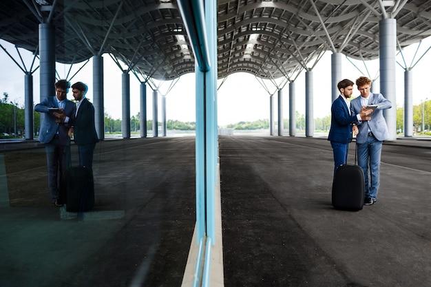 Obrazek dwa młodego biznesmena opowiada na staci i trzyma pastylkę odbijał w okno