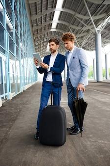 Obrazek dwa młodego biznesmena opowiada na terminal i trzyma pastylkę