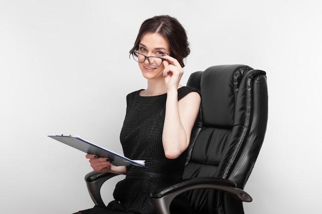 Obrazek ładna kobieta w czerni sukni z pastylką w rękach