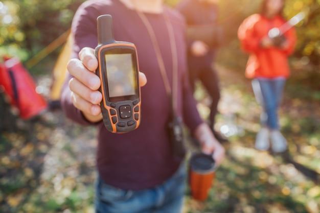 Obrazek mężczyzna trzyma telefon satelitarnego w ręce. młody mężczyzna i kobieta stoją za.