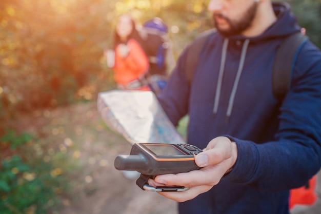 Obrazek młody brodaty mężczyzna trzyma satelitarnego telefon w ręce. w drugiej ręce jest mapa. młoda kobieta stoi za nim. ona ma plecak.