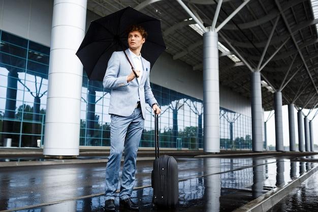 Obrazek młody redhaired biznesmen trzyma czarną walizkę w deszczu przy lotniskiem i parasol