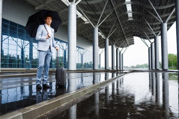 Obrazek młody redhaired biznesmen trzyma czarnego parasol w deszczu przy terminal