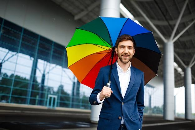 Obrazek młody rozochocony biznesmen trzyma pstrobarwnego parasol w dżdżystej ulicie