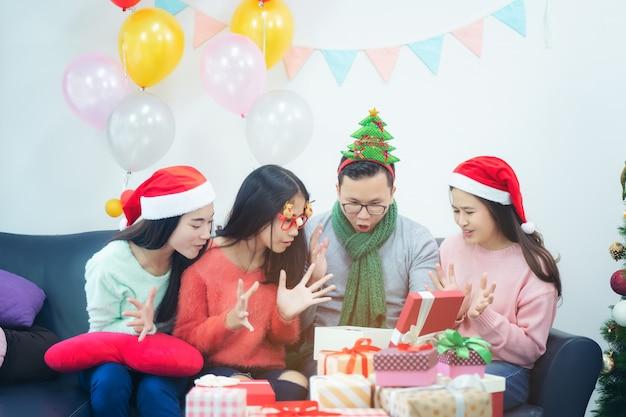 Obrazek pokazuje grupę przyjaciele świętuje boże narodzenia w domu. zaskoczony przyjaciel szczęśliwy w biurze