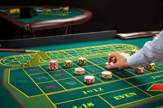 Obrazek przedstawiający zielony stół i zakłady z żetonami. mężczyzna przekazać żetony w kasynie na stole do ruletki. ścieśniać