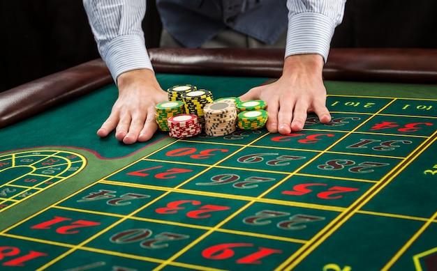 Obrazek przedstawiający zielony stół i zakłady z żetonami. mężczyzna przekazuje żetony w kasynie - zakład. ścieśniać