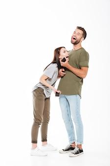 Obrazek roześmiana młoda kochająca pary pozycja odizolowywająca. patrząc na bok i trzymając telefony.