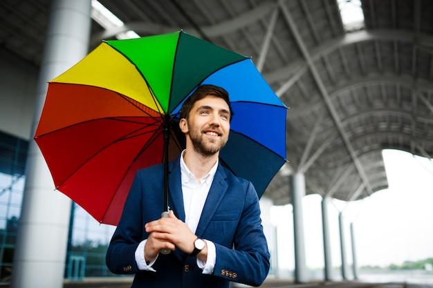 Obrazek rozochocony młody biznesmen trzyma pstrobarwnego parasol w ulicie