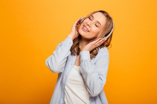 Obrazek śliczna caucasian kobieta 20s jest ubranym brasy w przypadkowej odzieży słucha muzyka używać bezprzewodowe słuchawki, odizolowywający nad kolor żółty przestrzenią