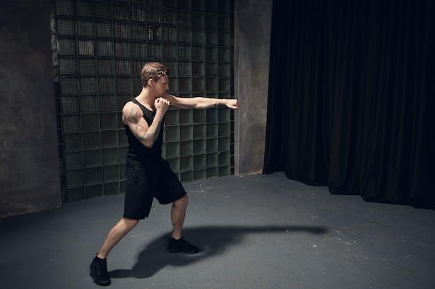 Obrazek stylowego, wysportowanego faceta rasy kaukaskiej z umięśnionymi wytatuowanymi ramionami, boksującego w pustym pokoju, wyciągającego jedną rękę, opanowującego ciosy podczas przygotowań do walki. ludzie, zdrowy tryb życia i sport