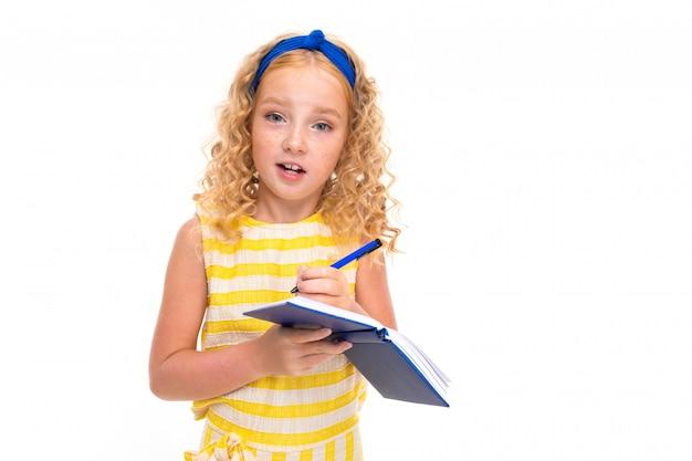 Obrazek szczęśliwe dziecko z uczciwym czerwonym kędzierzawym włosy ma dobry pomysł i pisze je notatnik odizolowywający na białym tle