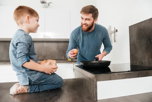 Obrazek szczęśliwy brodaty ojciec ubrany w niebieski sweter gotuje w kuchni ze swoim małym słodkim synkiem
