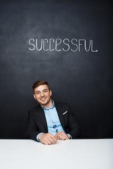 Obrazek szczęśliwy mężczyzna nad czerni deską z tekstem pomyślnym