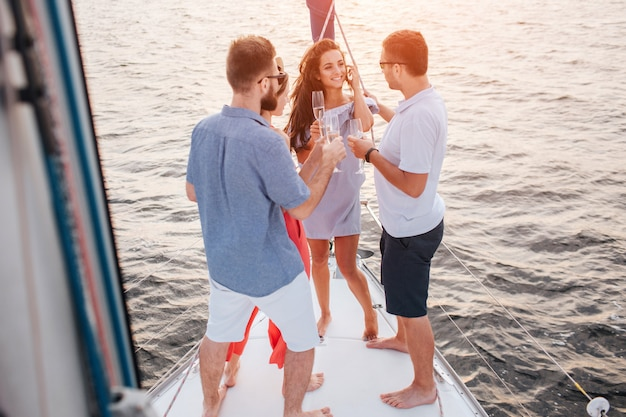 Obrazek trzy osoby patrzeje brunetki. rozmawiają z nią. uśmiecha się i patrzy na nich. ludzie stoją na dziobie jachtu. słońce zachodzi.