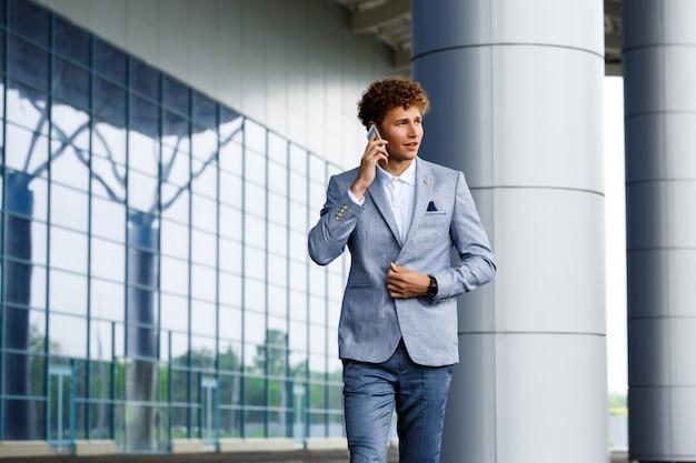 Obrazek ufny młody redhaired biznesmen opowiada na telefonie