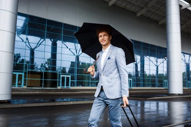 Obrazek uśmiechnięty młody redhaired biznesmena mienia parasol i walizka w deszczu przy lotniskiem
