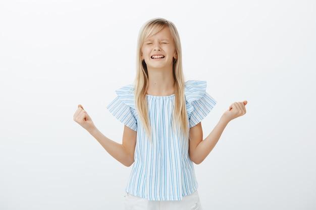 Obrażona dziewczynka jęcząca i płacząca, nieposłuszna. niezadowolona, zdenerwowana młoda córka o blond włosach, zaciskająca pięści i zęby, kłócąca się o słodycze, stojąca nad szarą ścianą
