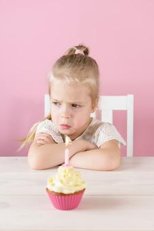 Obrażona dziewczynka z babeczką ze świecą na różowym tle