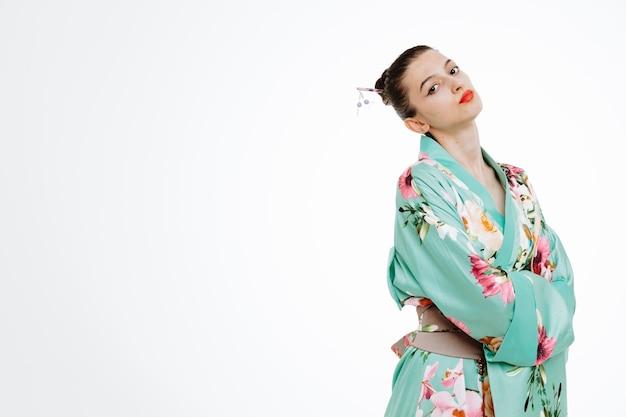 Obrażona kobieta w tradycyjnym japońskim kimonie jest zła na kogoś z rękami skrzyżowanymi na piersi na białym tle