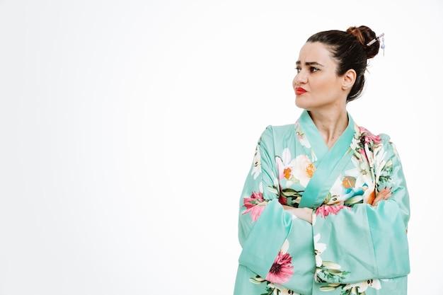 Obrażona kobieta w tradycyjnym japońskim kimonie, patrząca na bok z rękami skrzyżowanymi na piersi na białym tle