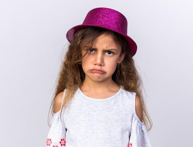 Obrażona mała kaukaska dziewczynka w fioletowym kapeluszu na białym tle na białej ścianie z miejscem na kopię