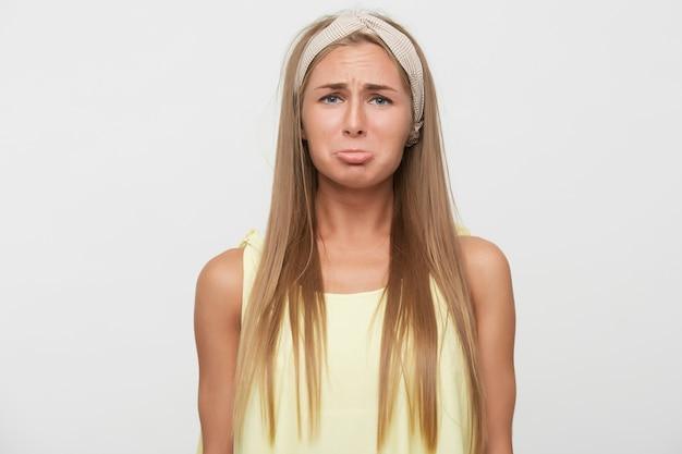 Obrażona młoda atrakcyjna długowłosa blondynka z przypadkową fryzurą wydymającą usta, patrząc na kamery z zdenerwowaną twarzą, ubrana w zwykłe ubrania, stojąc na białym tle