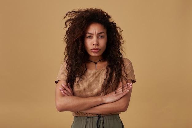 Obrażona młoda, dość kręcona ciemnoskóra brunetka dama składa ręce na klatce piersiowej, patrząc smutno i marszcząc brwi, pozując na beżu