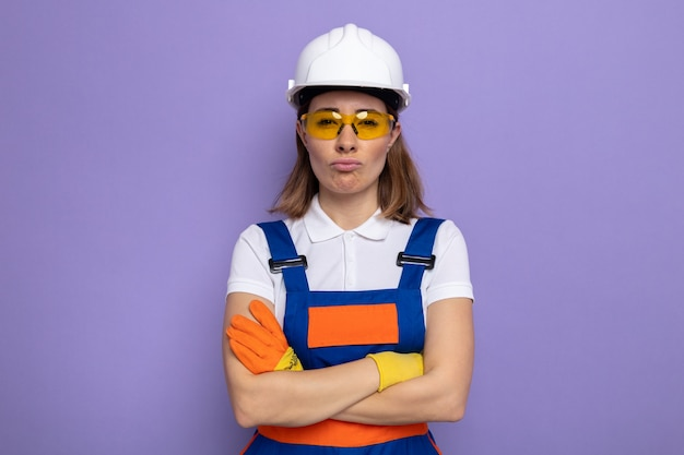 Obrażona młoda konstruktorka w mundurze budowlanym i kasku ochronnym w gumowych rękawiczkach w żółtych okularach ochronnych, zaciskając usta z rękami skrzyżowanymi, stojąc nad fioletową ścianą