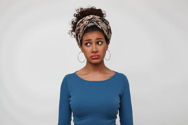 Obrażona młoda śliczna brunetka ciemnoskóra kobieta wykręca usta, patrząc smutno na bok, trzymając ręce wzdłuż ciała, stojąc na białym tle