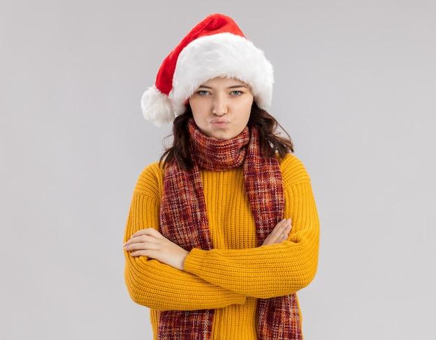 Obrażona młoda słowiańska dziewczyna w czapce mikołaja iz szalikiem na szyi stojąca ze skrzyżowanymi rękami na białym tle z miejsca na kopię
