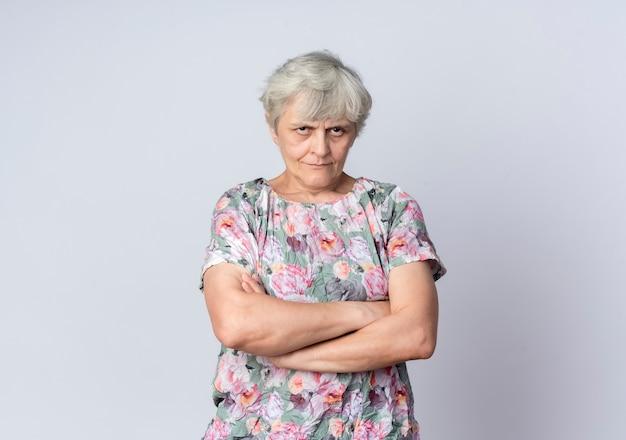 Obrażona starsza kobieta stoi ze skrzyżowanymi rękami na białym tle na białej ścianie