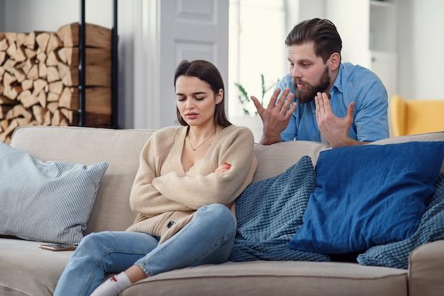 Obrażona zła kobieta siedzi na kanapie w domu po kłótni z mężem. zerwane małżeństwo.