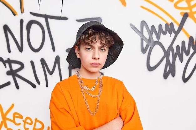 Obrażony niezadowolony nastolatek trzyma ręce skrzyżowane, wygląda nieszczęśliwie, nosi czarny kapelusz pomarańczowa koszulka z metalowymi łańcuszkami na szyi pozuje na ścianie z graffiti