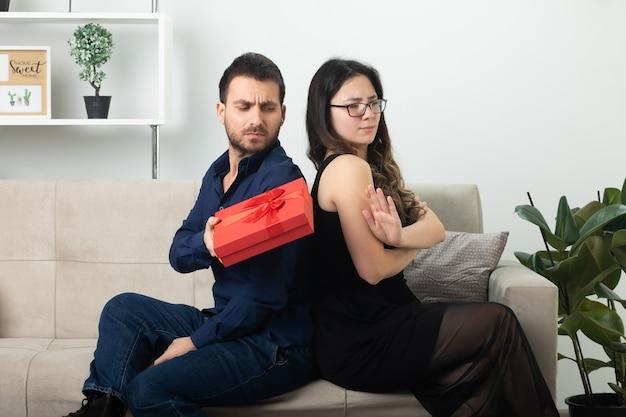 Obrażony przystojny mężczyzna daje pudełko niezadowolonej ładnej młodej kobiecie w okularach optycznych siedzącej na kanapie w salonie w marcowy międzynarodowy dzień kobiet