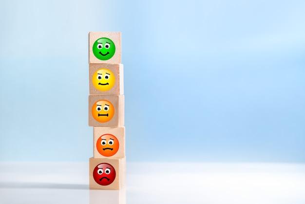 Obrazy emotikonów na drewnianych kostkach. koncepcje oceny obsługi klienta i badania satysfakcji. niebieskie tło z kopią przestrzeni