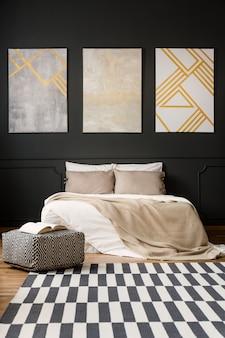 Obrazy na czarnej ścianie w sypialni
