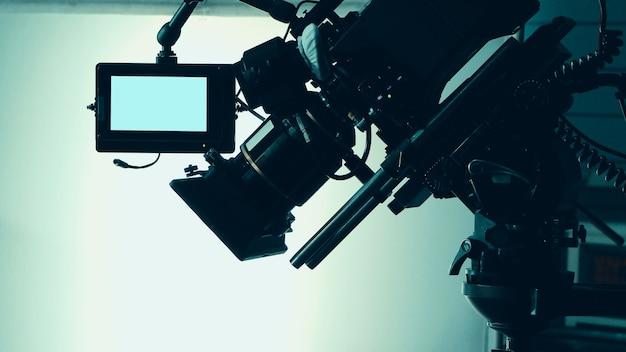 Obrazy sylwetki z kamery wideo w komercyjnej produkcji telewizyjnej, która obsługuje lub kręci kamerzystę i ekipę filmową w planie i rekwizycie na profesjonalnym dźwigu i statywie, aby były łatwe w użyciu