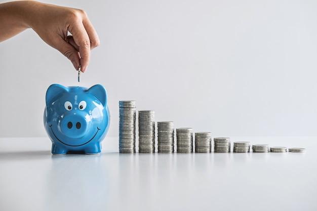 Obrazy układania monet i ręcznego wkładania monet do niebieskiej skarbonki w celu planowania wzrostu i oszczędności za pomocą skarbonki, oszczędzania pieniędzy na plan na przyszłość i koncepcji funduszu emerytalnego