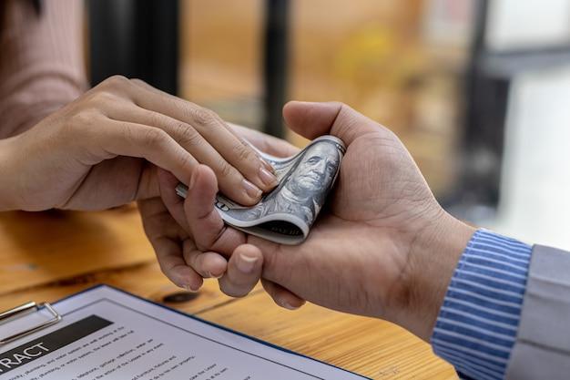 Obrazy z drugiej ręki przedstawiające ludzi, którzy wkładają w swoje ręce pieniądze, są partnerami biznesowymi, którzy zachowują się w nieuczciwy sposób, aby czerpać korzyści ze wspólnych projektów. oszustwa biznesowe i przekupstwo to nielegalne pojęcie.