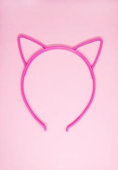 Obręcz do włosów w kształcie kocich uszu na delikatnym różowym tle. nowoczesny dodatek do włosów.