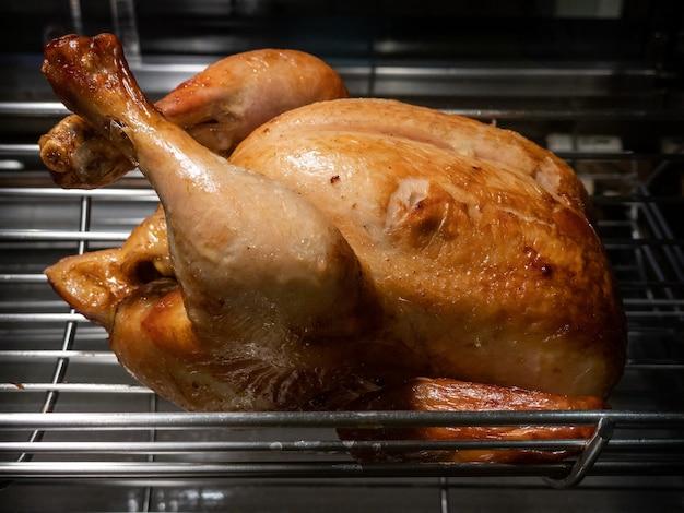 Obrotowa maszyna to grillowany cały kurczak. pieczone kurczaki z rzędu obracając się w przemysłowej palarni. pieczony szpikulec z grilla w komercyjnej rożnie.