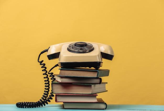 Obrotowy telefon na stosie książek. żółty