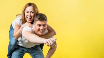 Obsługuje dawać jej roześmianej dziewczyny piggyback przejażdżce wskazuje przy kamerą przeciw żółtemu tłu