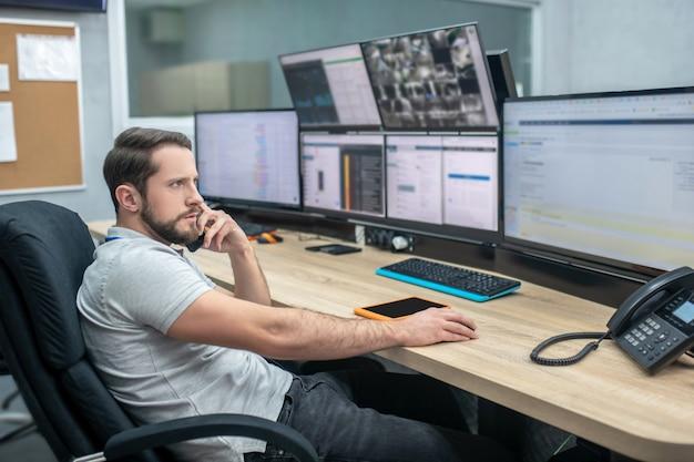 Obserwacja. zaangażowany obserwowanie poważnego mężczyzny z odznaką siedzącego na krześle przed monitorami dotykającego dłonią głowy
