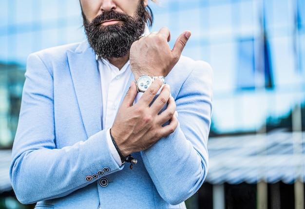 Obserwuj mężczyznę. biznesmen wskazuje na zegarek na tle miasteczka. mężczyzna trzyma zegarek. portret biznesmena w garniturze, za pomocą zegarka na tle miasta.