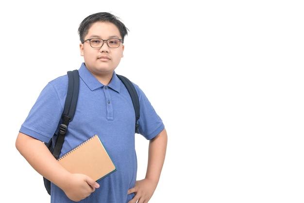Obsesyjnie uczeń chłopiec ubrany w niebieską koszulkę polo w okularach, trzymający notatnik na białym tle, powrót do koncepcji szkoły i edukacji