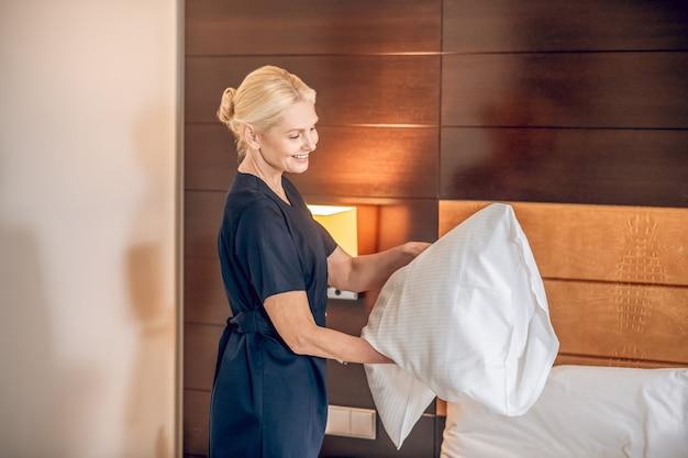 Obsługa hotelowa. blondynka ładna kobieta w mundurze ścieli łóżko w pokoju hotelowym